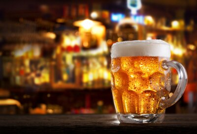cold mug of beer in a bar on wooden table