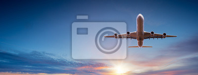Image Commercial airplane flying above dramatic clouds during sunset.