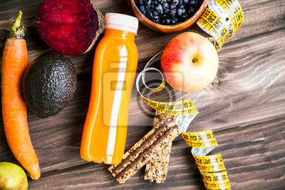 Concept de mode de vie sain avec bouteille de jus de fruits, de légumes et de fruits avec barres de muesli granola et ruban à mesurer sur une planche en bois, vue de dessus, concept de remise en forme