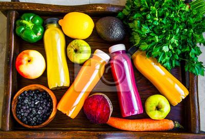 Concept de mode de vie sain avec des bouteilles de jus, des légumes et des fruits sur un plateau en bois, vue de dessus, concept de remise en forme de vie saine