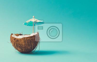 Image Concept de plage tropicale fait de fruits de noix de coco et parasol. Idée créative estivale minimale.