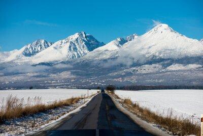 Image Conduite d'hiver - route d'hiver Route de campagne menant à travers un paysage de montagne d'hiver.