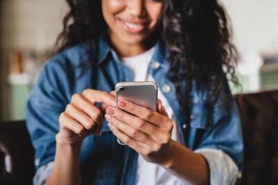 Image Cropped shot of an african-american young woman using smart phone at home. Smiling african american woman using smartphone at home, messaging or browsing social networks while relaxing on couch