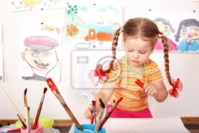 Enfant avec photo et un pinceau dans la salle de jeux.