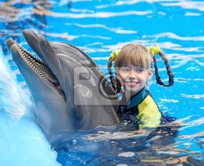 Enfant et dauphin dans l'eau bleue.