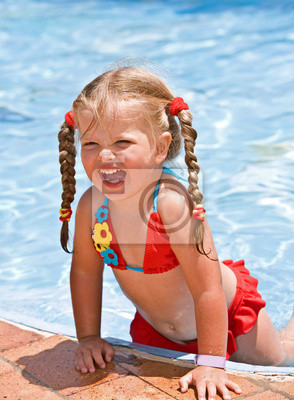 Enfant fille en bikini rouge près de la piscine bleue.