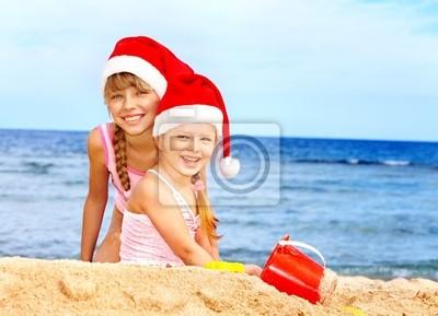 Enfants à santa chapeau jouant sur la plage.