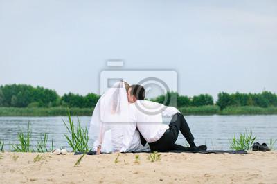 épris de mariage couple assis et embrassant près de l'eau