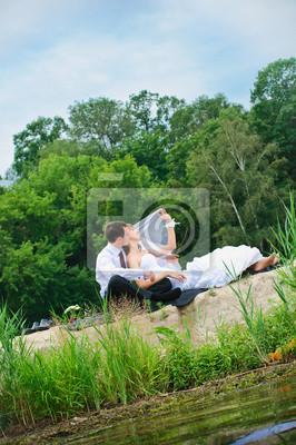 épris de mariage couple assis sur le sable près de l'eau