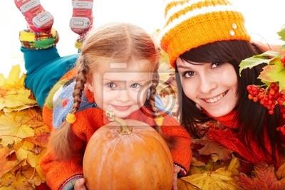 Famille heureuse avec le potiron sur des feuilles d'automne.
