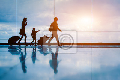Image Family at airport travelling with young child and luggage walking to departure gate, girl pointing at airplanes through window, silhouette of people, abstract international air travel concept
