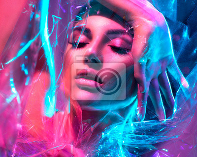 Image Fashion model woman in colorful bright neon lights posing in studio through transparent film. Portrait of beautiful sexy girl in UV. Art design colorful makeup