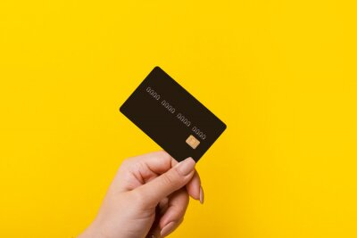 Image Female hand holding credit card on yellow background