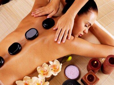 Image Femme adulte ayant le massage aux pierres chaudes dans le salon de spa
