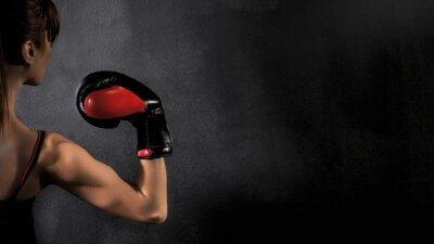 Image Femme Boxer avec biceps Red gant de boxe sur fond noir, le contraste avec filtre grunge saturé