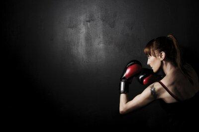 Image Femme Boxer avec des gants rouges sur fond noir, un contraste élevé avec filtre grunge désaturé en studio