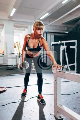 Femme dans la salle de gym faire seule rangée bras haltère