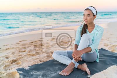 Femme de plage de yoga relaxant sur un tapis de fitness après une séance d'entraînement. Fit asiatique sportive asiatique faire l'exercice en vêtements de sport au coucher du soleil ou le lever du sol
