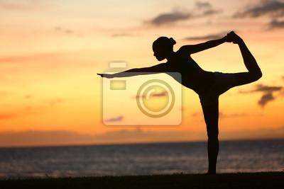 Femme de yoga au coucher du soleil serein à la plage faire poser