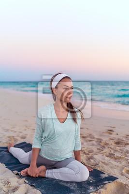Femme de yoga étirant des jambes en pigeon pose un étirement de jambe sur la plage au lever du soleil du matin. Mode de vie en bonne santé.