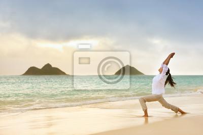 Femme de yoga méditant en guerrier pose à la plage
