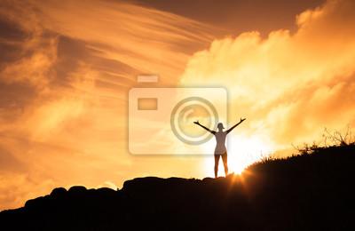 Image Femme debout sur une montagne, les bras en l'air. Bonheur, motivation et sentiment de bien-être.
