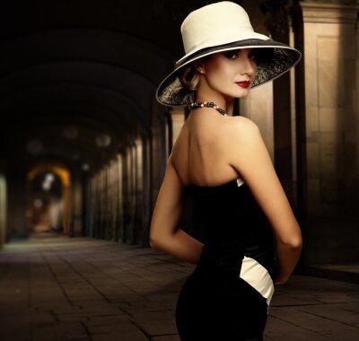 Image Femme en robe noire et grand chapeau blanc seule nuit à l'extérieur