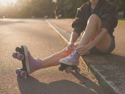 Image Femme mettant sur patins à roulettes dans le parc