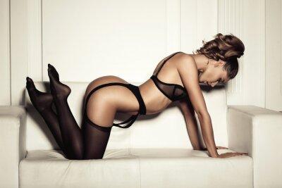 Image femme sexy en lingerie noire séduisante assis sur un canapé en sto