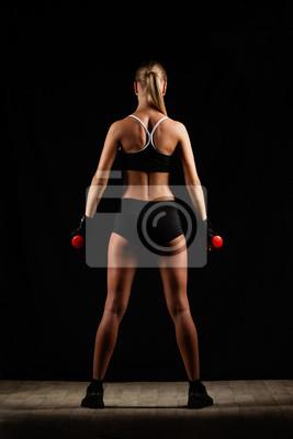 femme tenant des haltères rouges