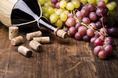 Image Fiasco di vino con uva e turaccioli su tavola di Legno