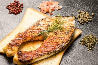 Image Filet de saumon grillé sur la tranche de pain chaud et les épices sur l'ardoise