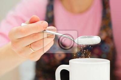 fille tient une cuillère et le sucre parsème de tasse