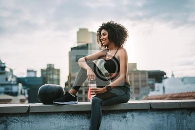Image Fitness femme assise sur le toit, prenant une pause de la séance d'entraînement