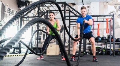 Image Frau und Mann im Fitnessstudio avec corde de bataille