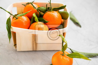 Fresh clementines citrus fruits in a basket, healthy organic clementines with leaves