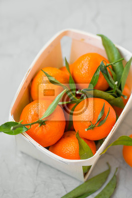 Fresh clementines citrus fruits in a basket top view, healthy organic clementines with leaves