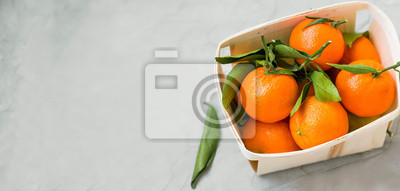 Fresh clementines citrus fruits in a basket with copy space, healthy organic clementines with leaves top view in a basket on concrete background copy space