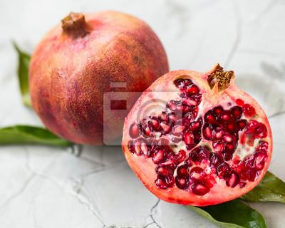 Fresh pomegranate fruit closeup. Whole and half of pomegranate fruit on concrete background