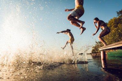 Image Friends having fun enjoying a summer day swimming and jumping at the lake.