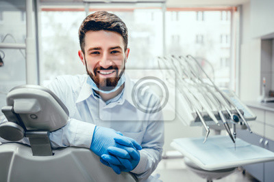Image Front view of professional male dentist in white doctor coat and protective gloves sitting in dental chair and equipment, looking at camera and smiling. Bearded man posing during working process.