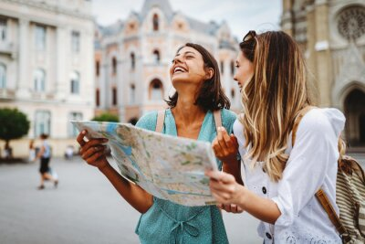 Image Fun, friends, travel and tourism concept. Beautiful girls looking for direction in the city