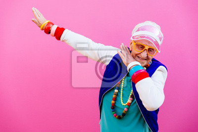 Image Funny grandmother portraits. 80s style outfit. Dab dance on colored backgrounds. Concept about seniority and old people
