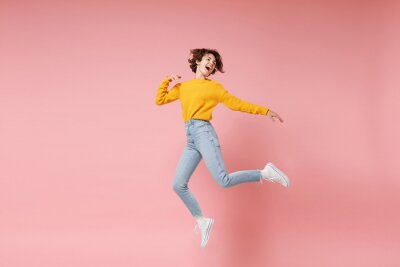 Image Funny young brunette woman girl in yellow sweater posing isolated on pastel pink background in studio. People lifestyle concept. Mock up copy space. Having fun fooling around, looking aside, jumping.