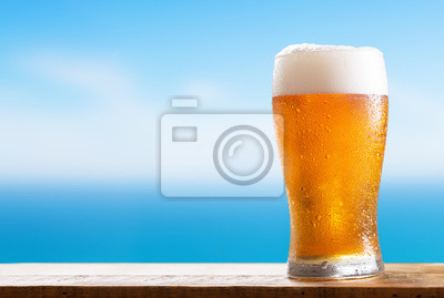 glass of beer on a wooden table on background of the sea