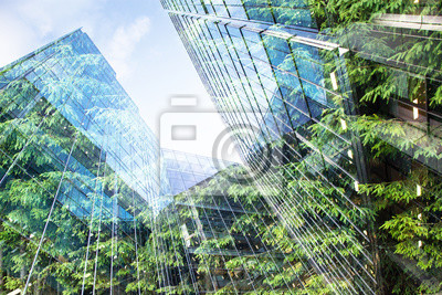 Image green city - double exposure of lush green forest and modern skyscrapers windows