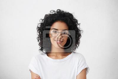 Image Gros plan d'un studio de jolie jeune modèle de race mixte avec des cheveux noirs et bouclés en regardant la caméra avec un joli sourire mignon tout en posant contre un espace vierge blanc pour votre c