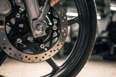 Image Gros plan de la main de l'homme tenant une clé de montage près du véhicule de la moto.