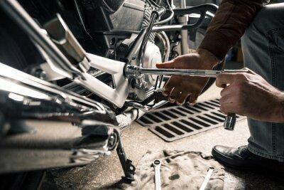 Image Gros plan des mains de l'homme avec une moto dans le garage