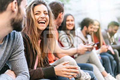 Image Group of trendy young people chatting together sitting on a bench outdoors. Students having fun together. Focus on a blonde girl smiling with open mouth
